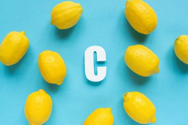Top view of ripe yellow lemons and letter C on blue background stock vector