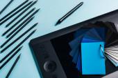 Top kilátás színes minták, grafika tabletta és színes ceruzák a kék háttér
