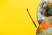 Top kilátás rajz ecset és paletták sárga felületen