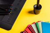 Közelkép a színes minták, grafikus tabletta és színes ceruzák sárga felületen