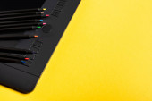 Zavřít pohled na barevné tužky na grafickém tabletu na žlutém povrchu