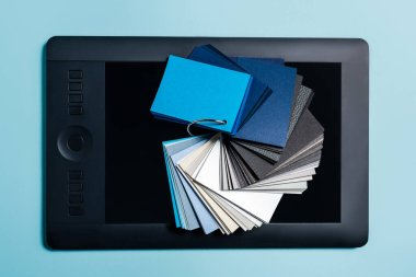 Top view of color samples on graphics tablet on blue background stock vector