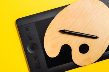 Top view of wooden palette and graphics tablet with stylus on yellow surface stock vector