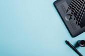 Horní pohled na barevné tužky na grafickém tabletu a stylus na modrém pozadí