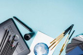 Horní pohled na barevné tužky, grafický tablet a akvarel kreslení na modrém pozadí