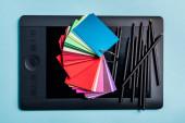 Horní pohled na barevné vzorky a tužky na grafickém tabletu na modrém pozadí