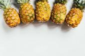 vrchní pohled na čerstvé zralé ananas se zelenými listy na bílém pozadí