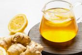 horký čaj v konvici na dřevěné desce u kořene zázvoru, citron na bílém pozadí