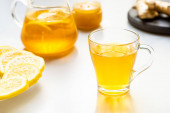 selective focus of hot tea in glass cup with lemon slices on white background