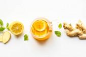 vrchní pohled na horký čaj ve skleněné konvice v blízkosti zázvoru kořen, citron a máta na bílém pozadí