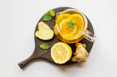 top view of hot tea in teapot served on wooden board with ginger root, lemon and mint on white background