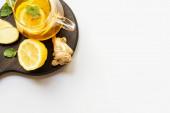 vrchní pohled na horký čaj v konvici podávané na dřevěné desce s kořenem zázvoru, citron a máta na bílém pozadí