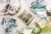 top pohled na cash roll s dolary v blízkosti zmačkané rubl bankovky izolované na bílém