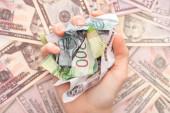 Fotografie oříznutý pohled na ženu držící zmačkané rublové bankovky v blízkosti dolarů
