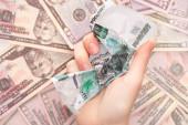 Fotografie pohled shora na ženu držící zmačkanou rublovou bankovku v blízkosti dolarů
