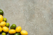 top view of colorful limes, avocado and lemons on grey concrete surface