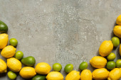 top view of colorful avocado, limes and lemons on grey concrete surface