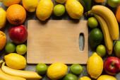 vrchní pohled na chutné barevné ovoce a dřevěné řezání deska