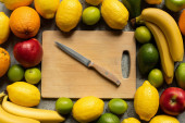top view of tasty colorful fruits and wooden cutting board with knife