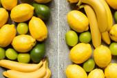 pohled na barevné banány, avokádo, citrony a citrony na šedém betonovém povrchu, koláž