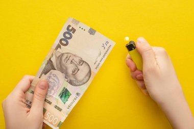 KYIV, UKRAINE - 25 Mart 2020: Sarı üzerinde izole edilmiş Ukrayna Hryvnia banknotunun yanında çakmak tutan kadın görüntüsü