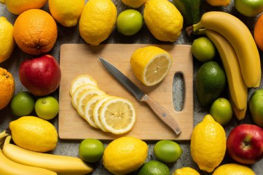 Top view of tasty colorful fruits and wooden cutting board with lemon slices and knife stock vector