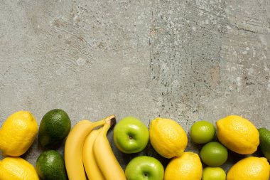 Top view of colorful bananas, apples, avocado, limes and lemons on grey concrete surface stock vector