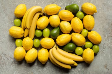 Top view of colorful bananas, avocado, limes and lemons on grey concrete surface stock vector