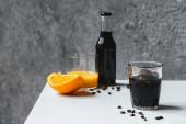 selektiver Fokus von kaltem Brühkaffee mit Eis im Glas und Flasche in der Nähe von Orangensaft und Kaffeebohnen auf weißem Tisch