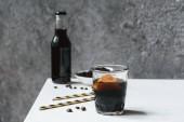 Selektiver Fokus von kaltem Brühkaffee mit Eis in Glas und Flasche in der Nähe von Trinkhalmen und Kaffeebohnen auf weißem Tisch