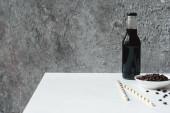 szelektív fókusz hideg főzet kávé jég palackban közelében ivószálak és kávébab fehér asztalon