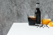 studená káva s ledem ve skle a láhvi v blízkosti pomerančového džusu a kávových zrn na bílém stole