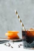 Selektiver Fokus von kaltem Brühkaffee mit Eis und Trinkhalm auf weißem Tisch