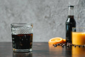 selective focus of cold brew coffee near bottle, orange juice and coffee beans