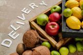 zralé čerstvé ovoce v dřevěných krabicích v blízkosti doručení slov na ošlehaném povrchu