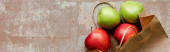 top view of paper bag with red and green apples on weathered beige surface, panoramic crop