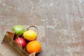 top view of paper bag with red and green apples, lemon and orange on weathered beige surface