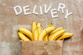 Photo top view of word delivery near paper bag with bananas on beige weathered surface