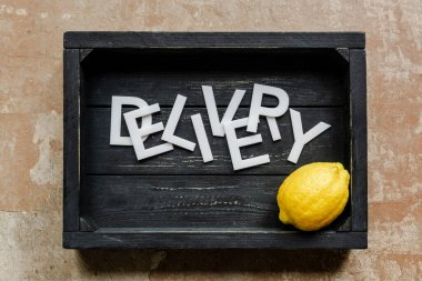 Top view of word delivery near lemon in wooden black box on weathered surface stock vector