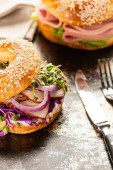 selective focus of fresh delicious bagel with meat, red onion, cream cheese and sprouts near cutlery on textured surface