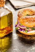 fresh delicious bagel with meat, red onion, cream cheese and sprouts on textured surface with bottle of oil