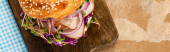 vrchní pohled na čerstvé lahodné bagety s masem, červenou cibulí, smetanovým sýrem a výhonky na dřevěné řezací desce a kostkovaným modrým ubrouskem, panoramatický záběr