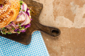 top view of fresh delicious bagel with meat, red onion, cream cheese and sprouts on wooden cutting board and plaid blue napkin