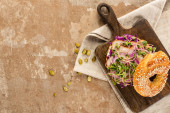Draufsicht auf frischen leckeren Bagel mit Fleisch, roten Zwiebeln und Rosenkohl auf Holzschneidebrett auf Serviette mit Kürbiskernen auf gealterter beiger Oberfläche