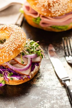 Selective focus of fresh delicious bagel with meat, red onion, cream cheese and sprouts near cutlery on textured surface stock vector