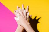 ořezaný pohled ženy mytí rukou s mýdlovou pěnou na růžové a žluté