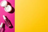 vrchní pohled na stříkací láhve s antiseptiky v blízkosti krém na ruce na růžové a žluté
