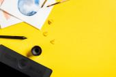 Fotografie Ansicht von Pinseln in der Nähe von Gemälden, Scherenschnittelementen, Zeichenblock und Stift auf gelb