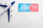 Horní pohled na letadýlko u dárkového poukazu s 200 hodnotami na bílém pozadí