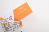 Horní pohled na dárkový poukaz s hodnotovým nápisem v nákupním košíku hraček na bílém pozadí